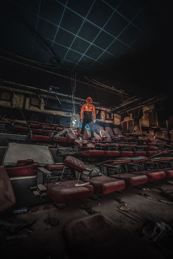 Digital composite image of man wearing mask while standing on broken chair in abandoned movie theater