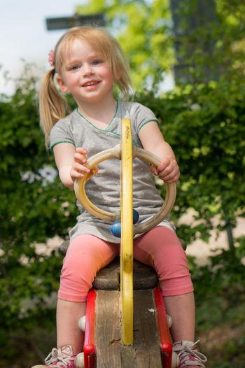 Full Length Portrait Of Smiling Girl On Seesaw At Park