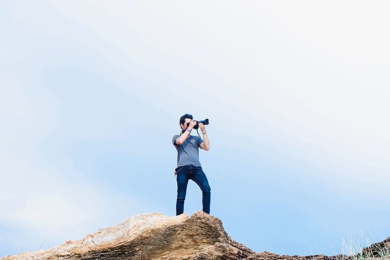 Low angle view of man photographing on mountain against clear sky