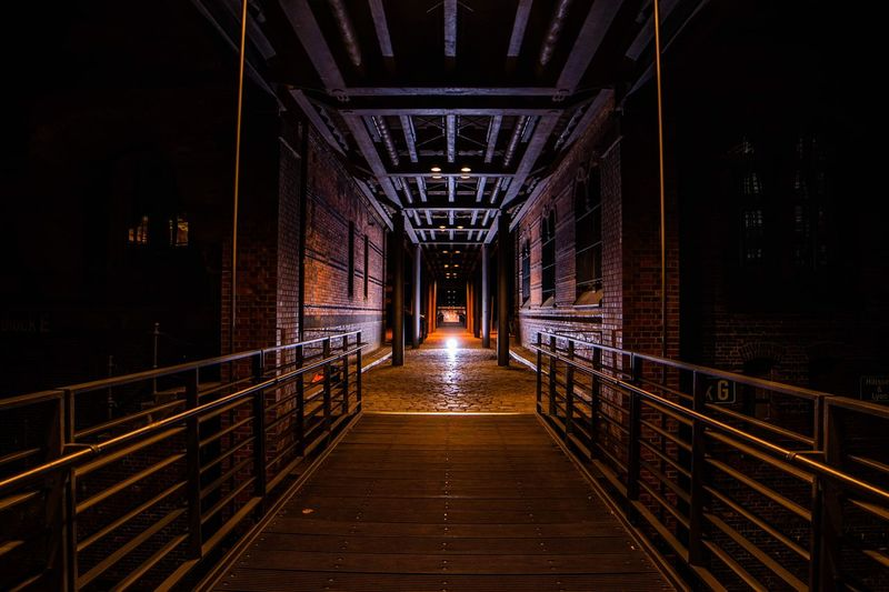 Diminishing Perspective Of Empty Footbridge At Night