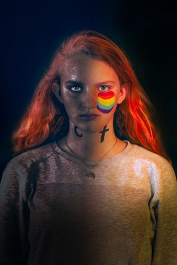 Portrait of teenage girl with face paint standing over black background