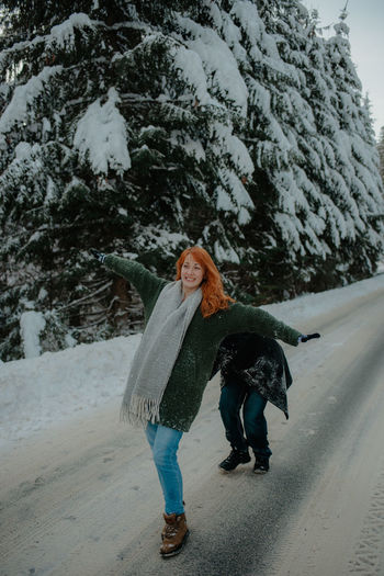 Full length of woman walking on snow covered road