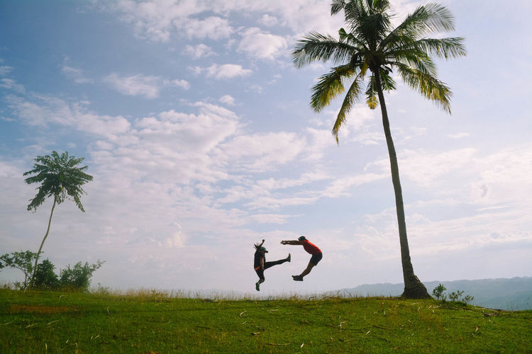 People jumping over grass by palm trees against sky