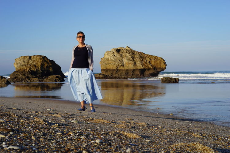 Full length of woman standing at beach against blue sky