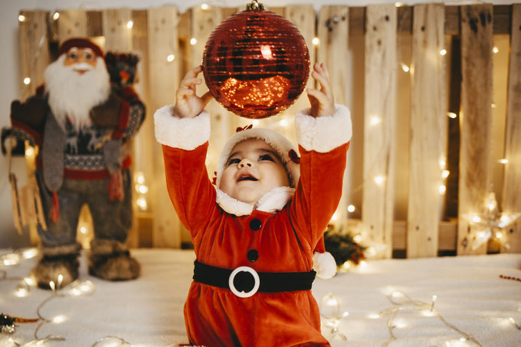 Full length of cute baby standing against illuminated christmas lights