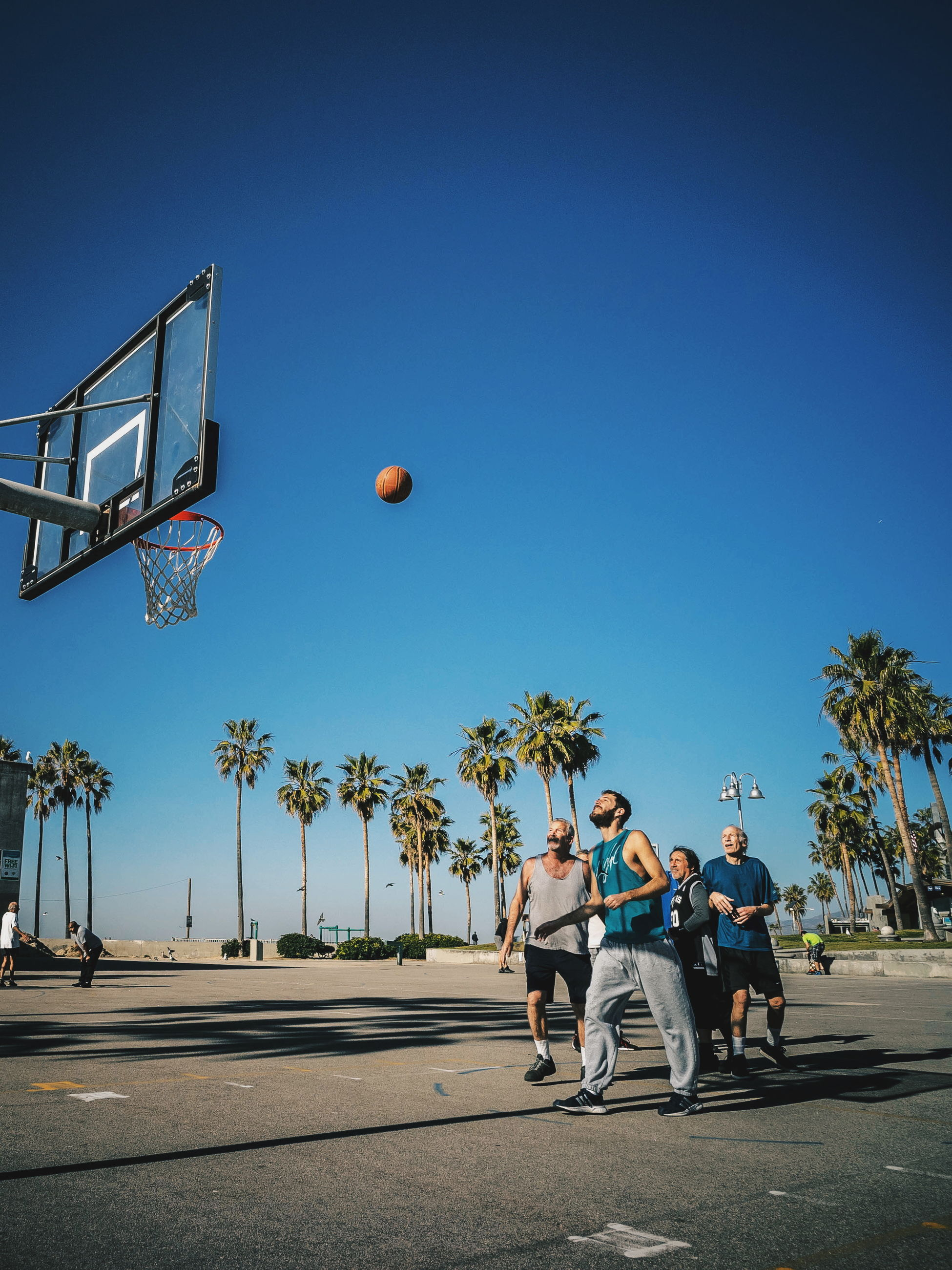basketball - sport, basketball hoop, full length, motion, ball, men, leisure activity, day, togetherness, blue, outdoors, lifestyles, playing, activity, jumping, mid-air, clear sky, real people, two people, sport, court, young adult, sky, adult, people