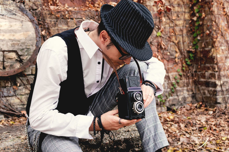 Male photographer using vintage medium format photo camera.