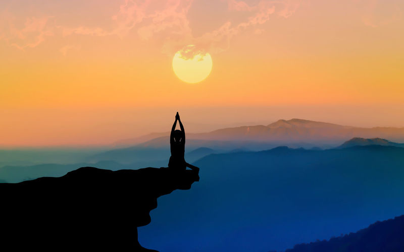 Silhouette Person Practicing Yoga On Cliff Against Sky During Sunset