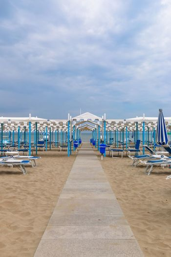 Empty beach, Italy, Riccione Italy. Riccione Italy Emiliaromagna Rimini Riccione Resort Chaise Lounge Sunbed Sunshade Canopy Umbrella Sand Beach Pathway Beach In A Row Sand Sea Sky Arrangement Cloud - Sky Shore Sun Lounger Outdoors Water Blue Day Vacations No People Tranquility