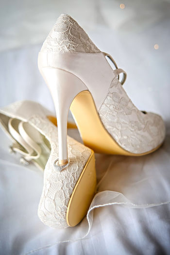 Close-up of white high heels on wedding dress