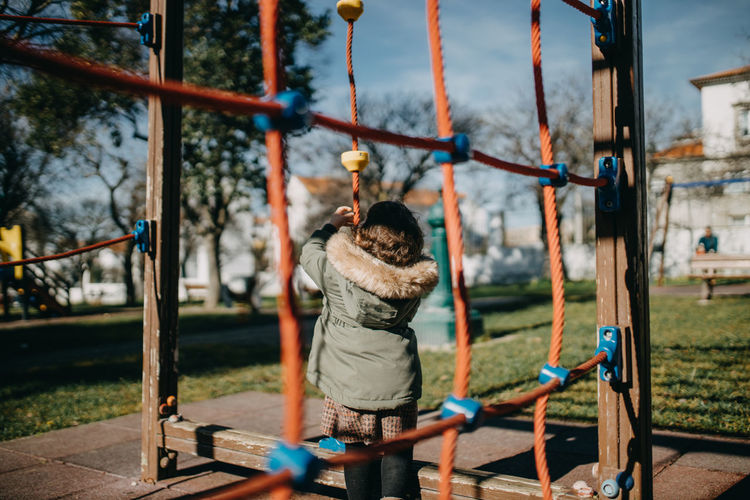 Rear view of child playing on playground