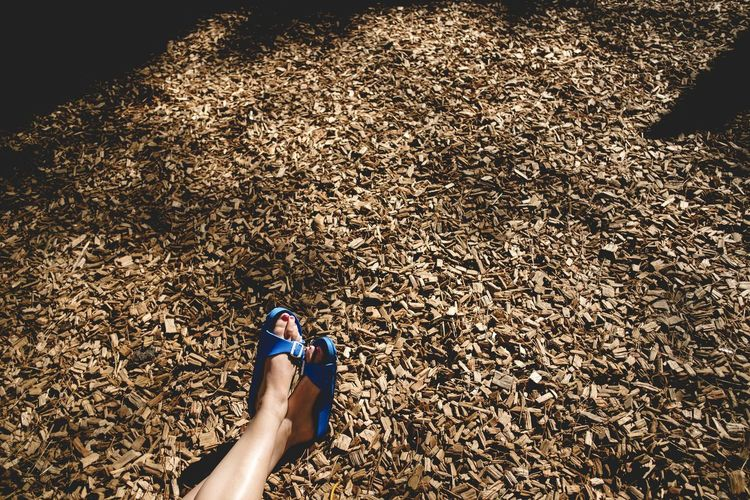 Low section of woman sitting on wood chips