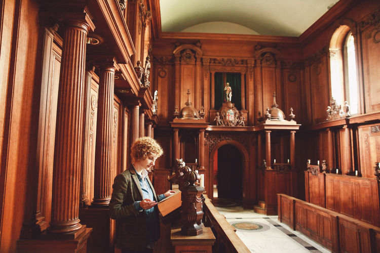 Young woman reading bible while standing in church