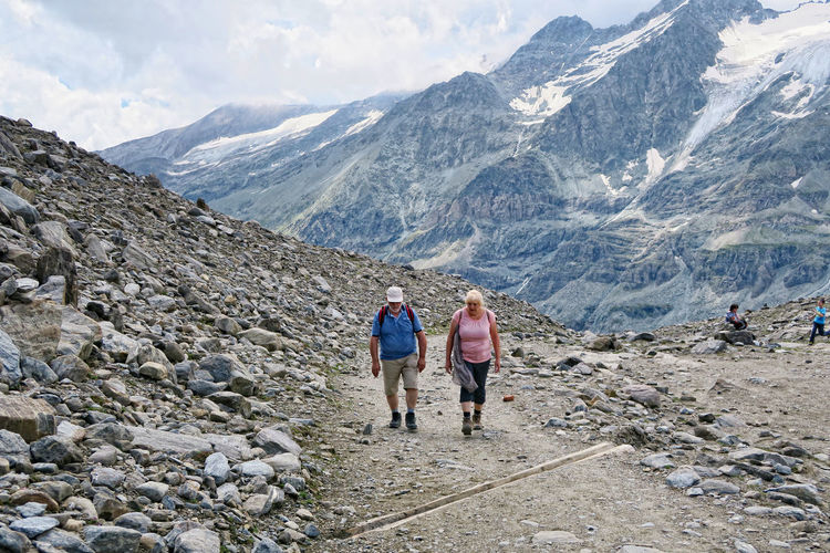 Mature hiking couple walking on dirt road at pasterze glacier against mountains