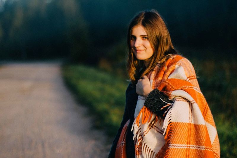 Portrait of smiling young woman with blanket standing on road