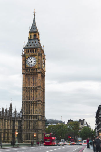 London, the big ben tower of the famous palace of westminster with urban traffic and tourists