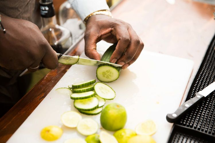 Man Cutting Cucumber In Kitchen