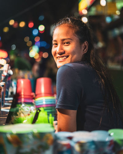 Bar Girl at Party One Person Women Real People Lifestyles Selective Focus Portrait Night Smiling Adult Hair Illuminated Focus On Foreground Young Adult Waist Up Casual Clothing Hairstyle Bare Tree Buckets Colourful Over Shoulder Bokeh Neon Lights Nightlife Small Business Strong Woman