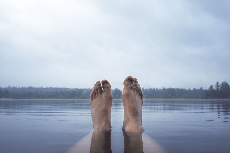 Low section of person relaxing in lake against cloudy sky