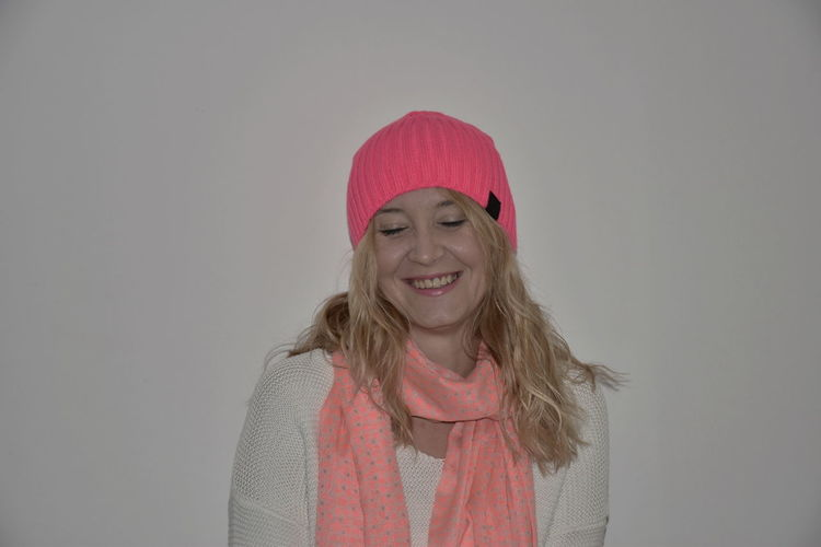 Smiling Woman In Warm Clothing Against Wall