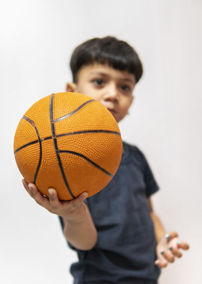 Portrait of boy with ball against white background