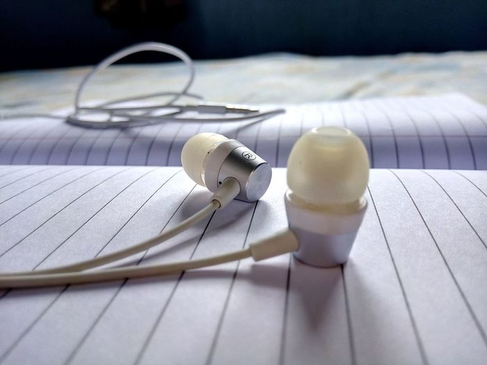 Close-up of in-ear headphones on book