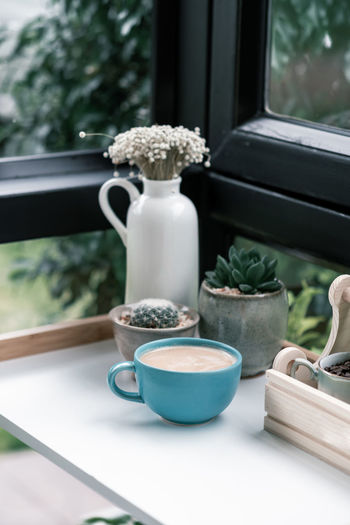 Close-Up Of Coffee Cup With Potted Plant On Window Sill