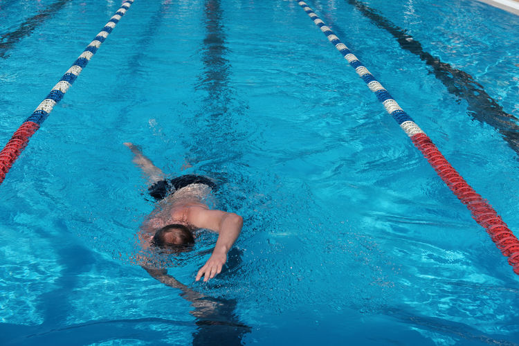 Middle age man swimming in open air pool. active lifestyle and leisure. sporty man enjoing swimming.