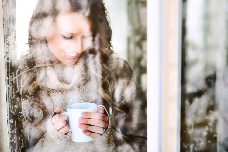 Beautiful woman enjoying coffee on a sunny winter day Coffee - Drink Cup Drinking Young Adult Winter Coffee Cup Drink Young Women Coffee Break Enjoyment Cafe One Person Women One Young Woman Only Beautiful Woman Smiling Window Frosty Frosty Window