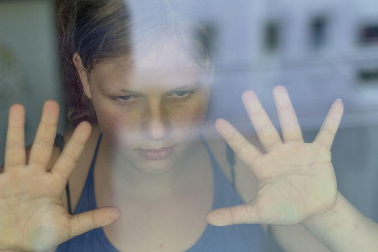 Teenage girl seen through glass window