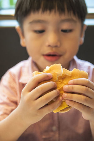 Portrait of a young kid holding burger. Focus on hands. 5 Years Old Asian  Burger Diet Hungry Young Boy Chinese Day Eating Focus On Foreground Food Hamburger Holding Indoors  Kid One Boy Only People Ready-to-eat Unhealthy
