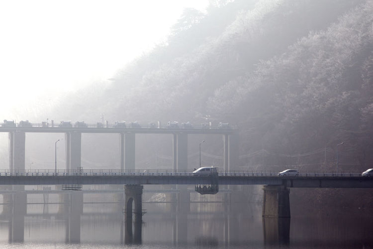 Cars on bridge over canal during foggy weather