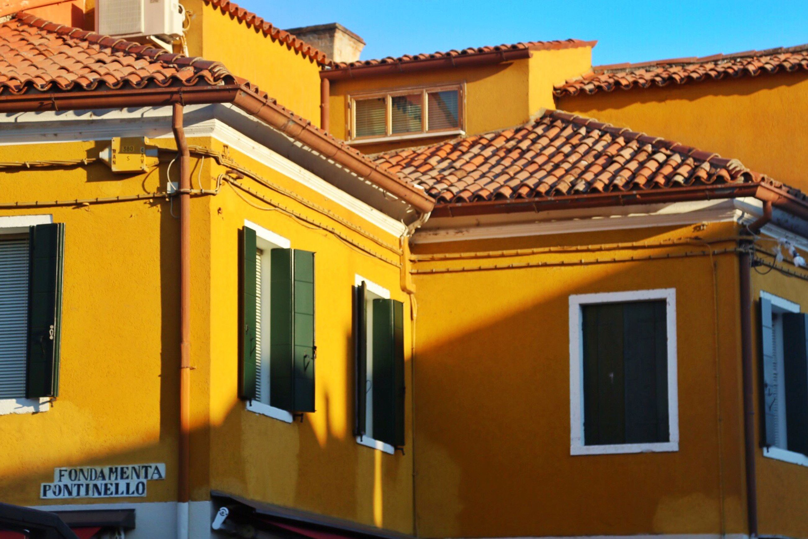 building exterior, architecture, built structure, yellow, window, house, roof, residential structure, residential building, day, sky, exterior, outdoors, high section, town, no people, city life