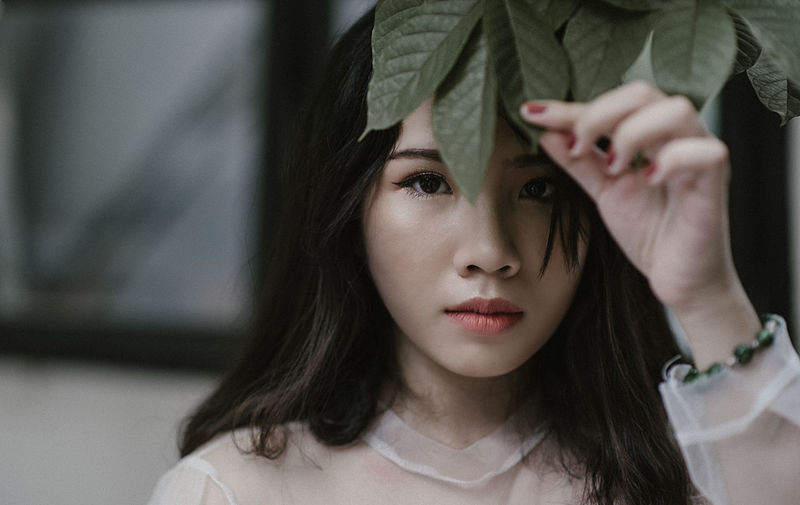 Close-Up Portrait Of Young Woman Holding Leaf