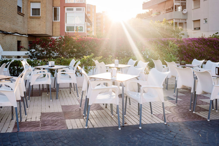 Chairs and tables at sidewalk cafe against buildings