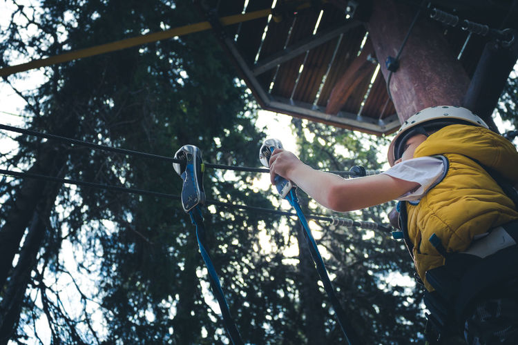 Low angle view of small boy attaching carabiner on a rope during canopy tour in adventure park.
