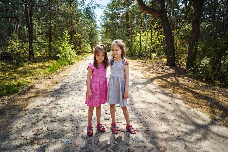 Full length of siblings standing on road amidst trees