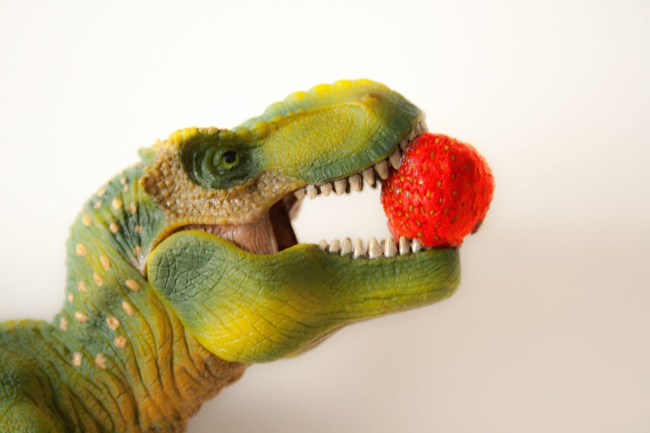 Dinosaur with strawberry in mouth