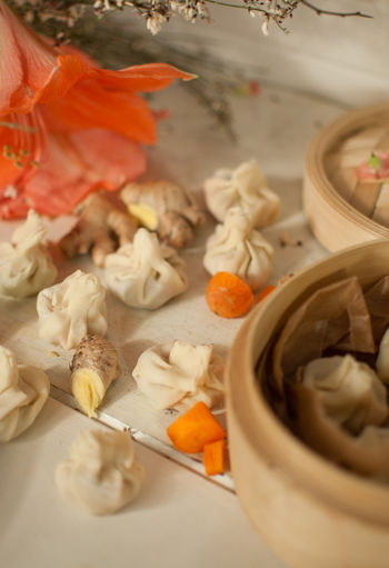 High angle view of dumplings and ginger by container on table
