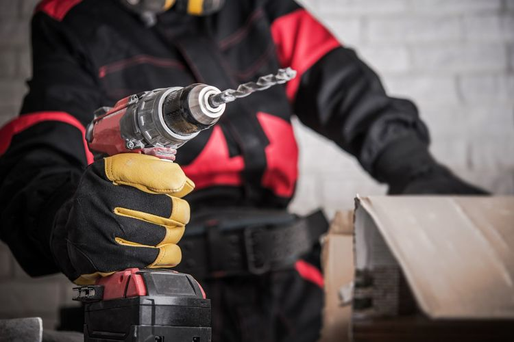 Construction Site Power Drill Tools. Contractor Worker with Powerful Cordless Drill Driver in Hand. Drilling Makes Easy Concept. Construction Working Close-up Day Drill Driver Headwear Holding Human Hand Men Midsection Occupation One Person Outdoors People Power Tool Protective Glove Protective Workwear Real People Skill  Standing Steel Worker Uniform Working