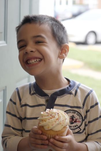 Happy boy holding cupcake while standing at doorway