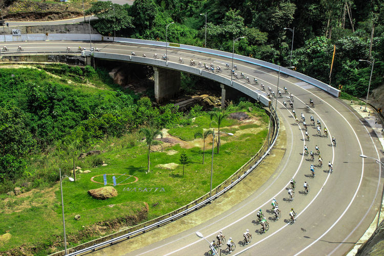High angle view of people doing bicycles racing on bridge