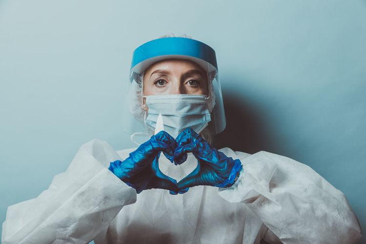 Portrait of doctor wearing mask making heart shape against wall