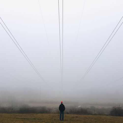 Man standing on field in foggy weather