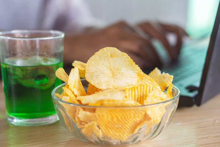 Woman eating potato chips with soda glass at work