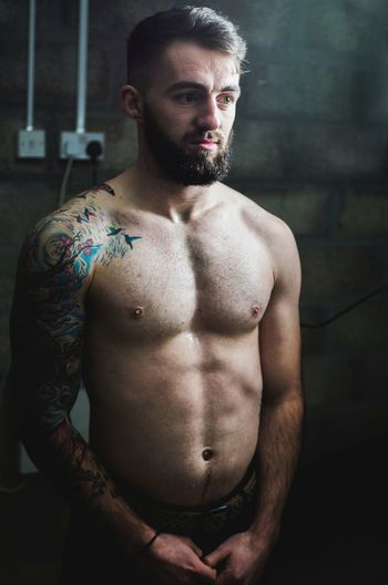 Thoughtful shirtless man standing against wall