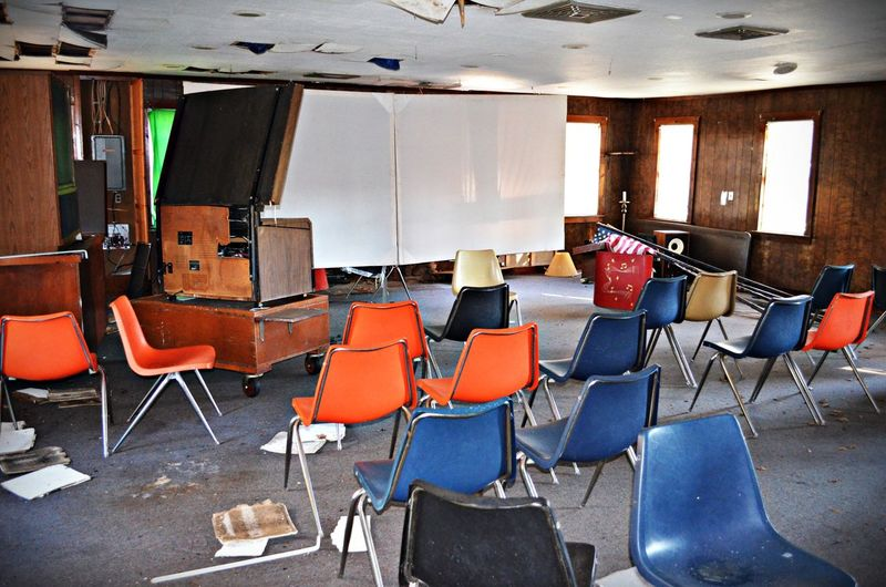 Abandoned interior with chairs and projection screen