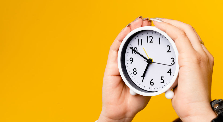 Close-up of hand holding clock against yellow background