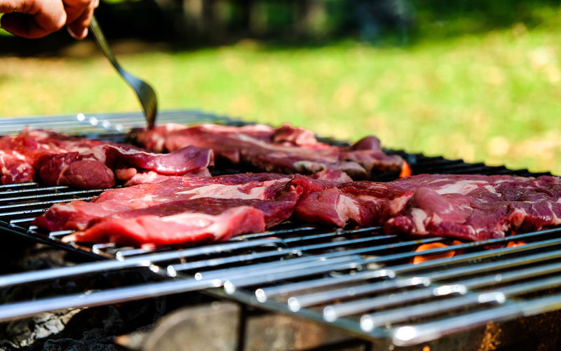 Cropped hand preparing meat on barbecue grill