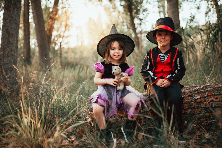 Portrait of happy friends sitting on land